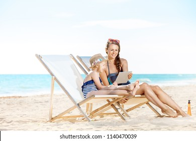 smiling young mother and child in swimwear on the seashore using tablet PC while sitting on beach chairs