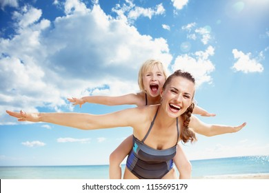 smiling young mother and daughter in beachwear on the seacoast rejoicing