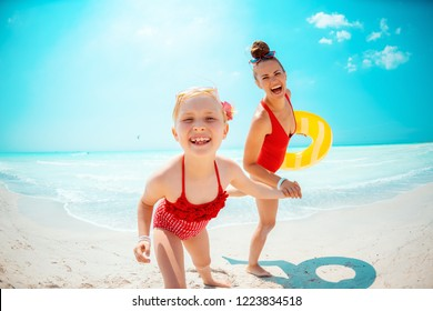 smiling young mother and daughter in red swimsuit with yellow inflatable lifebuoy on the beach