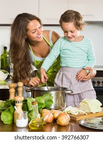Smiling young mother with little daughter cooking at home kitchen