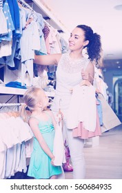 Smiling young mother with small daughter girl  buying clothes in kids apparel boutique