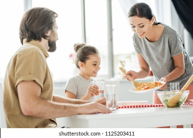 smiling young mother with tasty breakfast for daughter and husband at kitchen