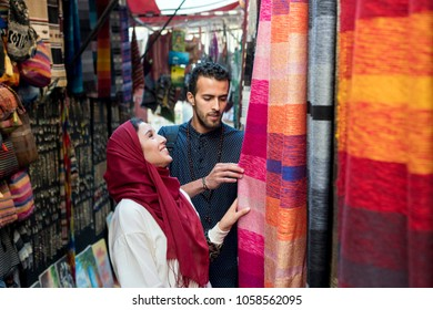 Smiling young muslim couple shopping and looking at carpets in a textile store