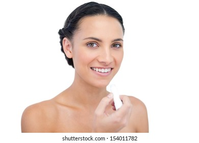 Smiling young natural model applying chap stick on white background