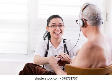 Smiling young nurse taking care about senior man with headset
