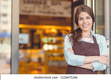 Smiling young owner in uniform in the bakery