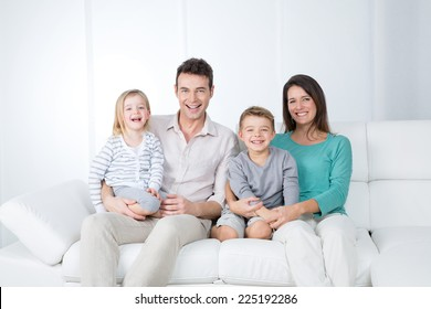 smiling young parents on white sofa