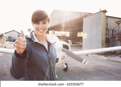 Smiling young pilot posing at the airport and giving a thumbs up, propeller plane on the background, travel and aviation concept