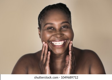 Smiling young plus size African woman with a perfect complexion standing with her hands on her chin against a warm sand colored background