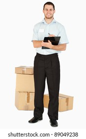 Smiling young post employee with parcels and clipboard against a white background