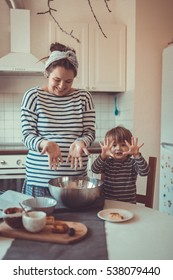 smiling young pregnant mother with dreadlocks is preparing in the kitchen with her son Toddler, make the dough for baking bread, lifestyle, toning, real interior