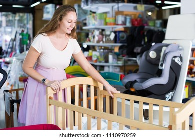 Smiling young pregnant woman closely choosing cradle for unborn baby