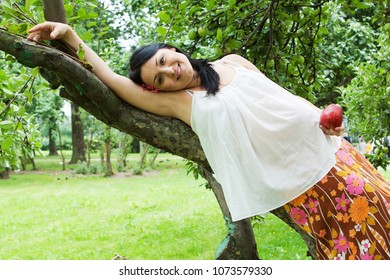 smiling young pregnant woman rests in a summer apple garden