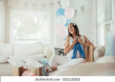 Smiling young pregnant woman sitting on sofa with new gifts at baby shower party. Expecting mother looking at baby clothes and smiling.