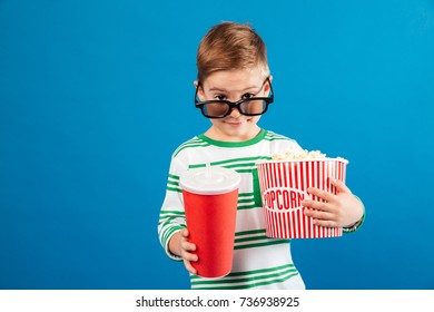 Smiling young preparing to watch the film and looking over eyeglasses at camera while holding soda and popcorn isolated blue background