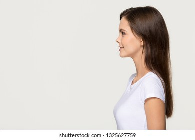 Smiling young pretty woman standing in profile looking forward at copy space, confident ambitious teen girl thinking of leadership future goals isolated on white grey background, side view portrait