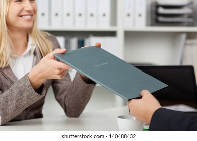 smiling young professional passing her CV to businessman