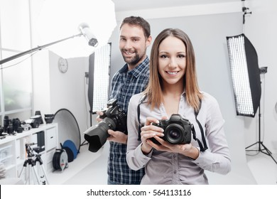 Smiling young professional photographers posing in the studio, they are holding digital cameras