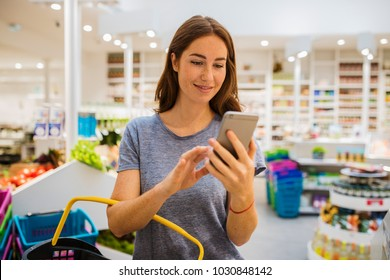 Smiling young red head woman, using her cellphone in modern market