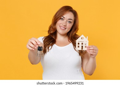 Smiling young redhead plus size body positive female woman girl 20s in white casual t-shirt posing hold in hands house bunch of keys looking camera isolated on yellow color background studio portrait