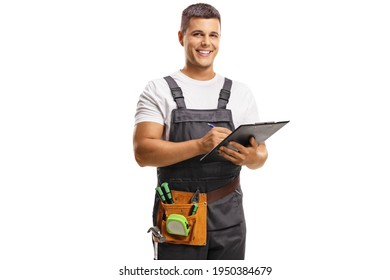 Smiling young repairman with a tool belt writing on a clipboard isolated on white background