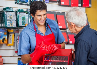 Smiling young salesman showing drill bit to senior man in hardware store