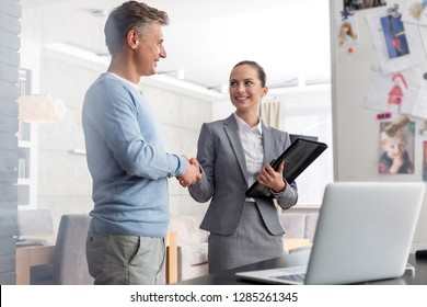 Smiling young saleswoman shaking hands with mature man in apartment