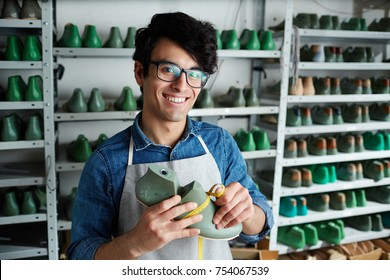 Smiling young shoe repairman with workpiece and measuring tape looking at camera