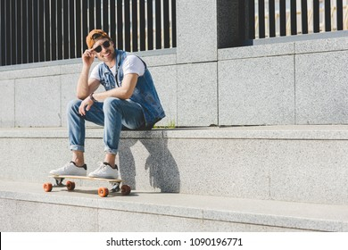 smiling young skater sitting on stairs with longboard looking away