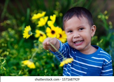 Smiling young son giving an arrangement of yellow flowers he is holding to show affection and love.