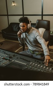 smiling young sound producer sitting at studio