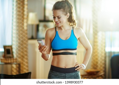 smiling young sports woman in fitness clothes in the modern living room wearing heart rate monitor using smartphone to track heart rate in fitness app.