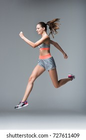 smiling young sportswoman jogging and looking away isolated on grey
