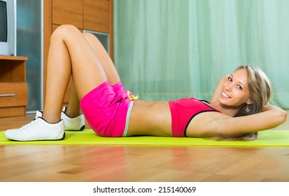 Smiling young sporty girl working out with dumbbells at home