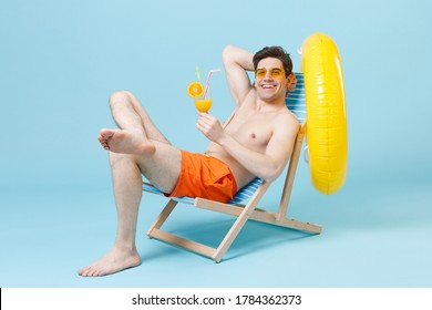 Smiling young strong fitness body man guy in orange shorts glasses sit on deck chair isolated on blue background studio portrait. People summer vacation rest lifestyle concept. Hold glass of cocktail