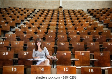 Smiling young student in empty lecture hall