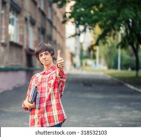 Smiling young student man holding a book, tablet and thumbs up against a city background