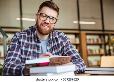 Smiling young student sitting at the desk in library and looking at camera