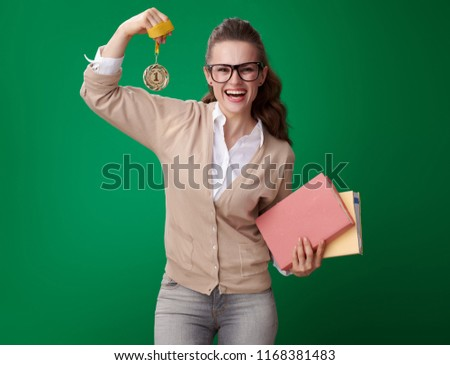 smiling young student woman with books showing medal and biceps isolated on green background