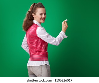 smiling young student woman in a red waistcoat writing with a piece of chalk isolated on green background
