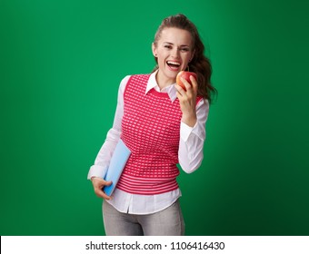 smiling young student woman in a red waistcoat with a blue notebook biting an apple isolated on green background