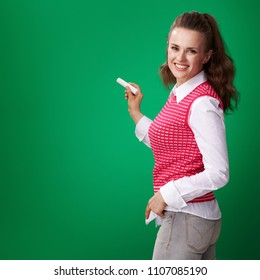 smiling young student woman in a red waistcoat writing with a piece of chalk on green background