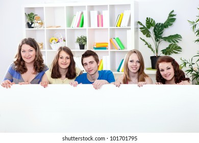 smiling young students holding big empty paper for commercials
