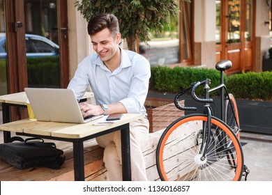 Smiling young stylish man in shirt working on laptop computer while sitting at a cafe outdoors with bicycle