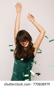 Smiling young stylish woman posing with hands up in falling green confetti.