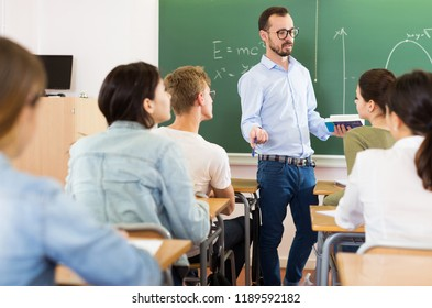 smiling young teacher is giving lecture for students in the class.