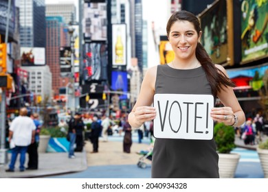 A smiling young in Times Square holding a 'VOTE' sign.