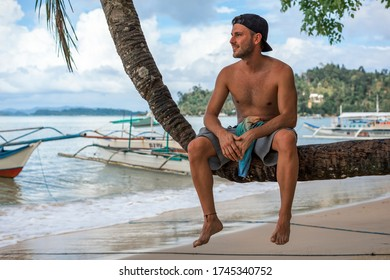 A smiling young tourist man sitting on a bent palm tree next to the beach in Port Barton, Palawan, Philippines (front view)