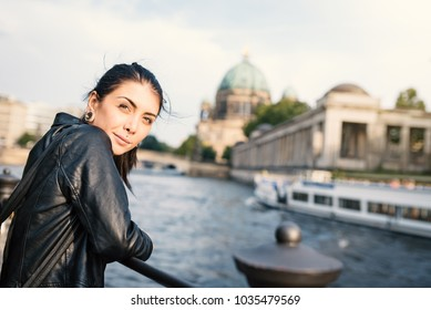 Smiling young tourist woman portrait in Berlin. Island Museum in the background. Lifestyle concept.