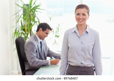 Smiling young tradeswoman with colleague sitting behind her